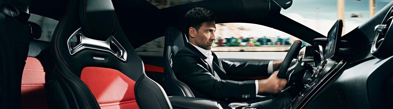 Un bărbat aflat în interioriorul luxos al unui Mercedes-Benz se bucură de o experiență deosebită de condus.